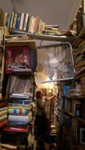 A bridge of books over the other books. The fan isn't supported by anything but wishful thinking.